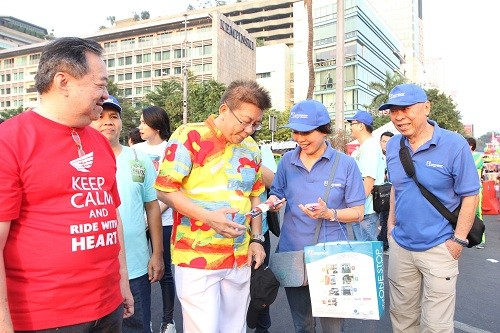 Tampak pada gambar: (ki-ka berbaju biru) Liana Setiawan – Sales Director PT Datascrip dan Joe Kamdani – Chairman & Founder pt. Datascrip memberikan cinderamata sebagai salah satu wujud apresiasi kepada peserta Parade Simpatik Hari Pelanggan Nasional 2015 di Jakarta pada Minggu, 6 September 2015.